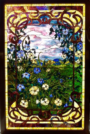 """A Spring Evening"" is a lovely stained glass panel.  Its colors and shading are notable. Much of the border is composed of Kokomo Catspaw granite, while the interior glass is mostly Youghiogheny ring mottles and stipple."