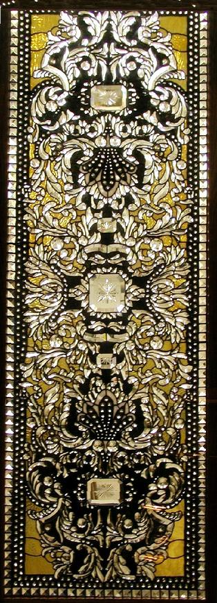The design in this window is very complex. There are over 1000 bevels and over 1000 jewels in this piece. It measures approximately 2'x6' and is called Baroque Banquet.
